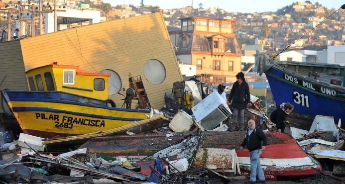 Varias personas caminan hoy, jueves 17 de septiembre de 2015, entre los destrozos causados por el tsunami posterior al terremoto 8,4 de magnitud en la escala de Richter que anoche sufrió Chile, en el puerto de la localidad costera de Cquimbo (Chile). (EFE)